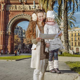 Mother and child near Arc de Triomf in Barcelona looking at map. In Barcelona for a perfect winter. happy young mother and child near Arc de Triomf in Barcelona Royalty Free Stock Photo
