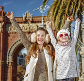 Mother and child near Arc de Triomf in Barcelona rejoicing. In Barcelona for a perfect winter. Portrait of happy trendy mother and child near Arc de Triomf in Royalty Free Stock Photo