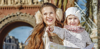 Mother and child near Arc de Triomf holding map and pointing. In Barcelona for a perfect winter. Portrait of happy modern mother and child near Arc de Triomf in Royalty Free Stock Photo