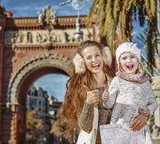 Mother and child near Arc de Triomf with map showing thumbs up. In Barcelona for a perfect winter. Portrait of smiling trendy mother and child near Arc de Triomf Stock Photography