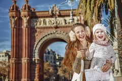 Mother and child near Arc de Triomf with map showing thumbs up. In Barcelona for a perfect winter. Portrait of smiling trendy mother and child near Arc de Triomf Royalty Free Stock Photos