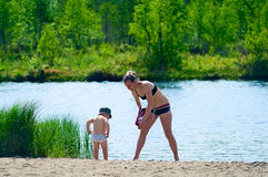 Mother And Child Near A Lake. Mother and little child are on the sand near river. They are going to swim together. Woman persuades the child to go in water Royalty Free Stock Photography
