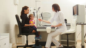 Mother and child in the ophthalmologist`s room- optometrist in clinic checking little child`s vision Royalty Free Stock Image