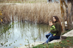 Mother with child outdoor. Young mother walking with her little son outdoors in autumn Stock Photo