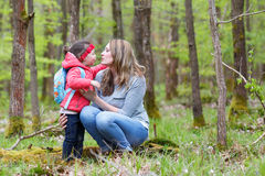 Mother and child outdoors playing, kissing and hugging Stock Photos