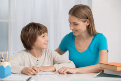 Mother and Child Parenting Motherhood Love Care Concept. Mother young women helping her child to do homework royalty free stock photography