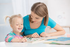 Mother and Child Parenting Motherhood Love Care Concept. Mother young women sitting with her child reading a book royalty free stock image