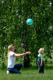 Mother and child play with ball. In park Stock Photography