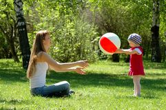 Mother and child play with ball. In park Stock Photo