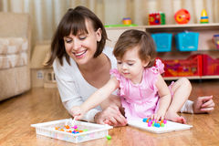 Mother and child play mosaic toy together indoors Stock Image