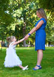 Mother and child play on outdoor, woman and girl in city park, summer season. Mother and child play on outdoor, women and girl in city park, summer season Stock Image
