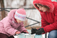 Mother with child play with snow on bench Stock Photos