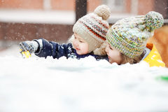 Mother with child play in snow on winter walk, positive emotions, outdoor. Snowfall, blizzard. Mother with child playing on winter walk at city, positive Stock Photos