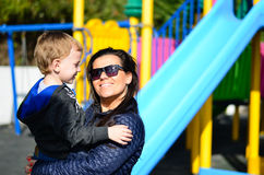 Mother and  child on the playground. Cute  fashion smiling boy sitting with his mom at the playground in a sunny day Stock Image