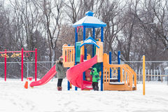 Mother and child at playground in snow Royalty Free Stock Photo