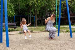 Mother and child at playground swinging Stock Photo
