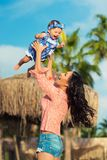 Mother and child playing on the beach. Mom throws up the baby. royalty free stock photo