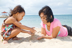 Mother and child playing with beach sand stock image