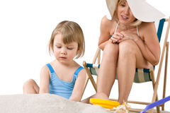 Mother with child playing with beach toys Stock Images