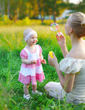 Mother and child playing blowing soap bubbles on the grass Stock Photography