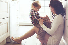 Mother and child playing with cat. Mother with her baby playing with pet on the floor at the kitchen at home Royalty Free Stock Photos