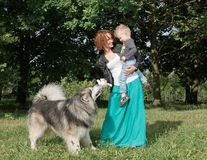 Mother and child playing with dog on nature. Stock Photos