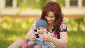 Mother and child playing a game with phone on grass stock footage