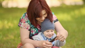 Mother and child playing a game with phone on grass stock video footage