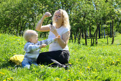 Mother and child playing on green field Royalty Free Stock Images