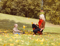 Mother and child playing and having fun in autumn Stock Images