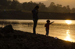 Mother and child playing on a lakeside Royalty Free Stock Photo