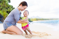 Mother and child playing and laughing on beach shore. Mother and daughter having a good time together at the beach Royalty Free Stock Photos