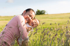 Mother and child playing and laughing in a outdoor green field. Young girl and 1 yo baby hugging in a grassy field Royalty Free Stock Photography