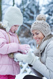 Mother and child playing in snow Stock Photography