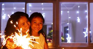 Mother and child playing with sparklers. Image of a happy mother and her daughter playing with sparklers at Christmas time stock photography