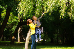 Mother and child playing at summer city park on nature Stock Photos