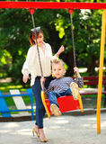 Mother with child playing on swing playground in summer  park Stock Image