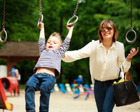 Mother with child playing on swing playground in summer  park Stock Images