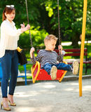 Mother with child playing on swing playground in summer  park Royalty Free Stock Photos