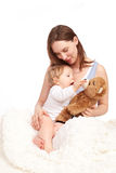 Mother and child playing with teddy. Young Mother and pretty child stock image