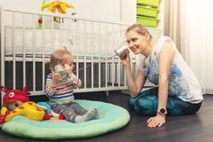 Mother and child playing with tin can phone at home royalty free stock photos