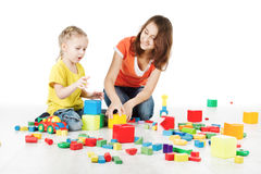 Mother and child playing toys blocks. Mother and daughter playing toys blocks over white background Royalty Free Stock Image