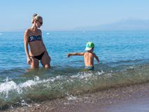 Mother and child playing at tropical beach. Family sea summer vacation. Mom and kid boy play and build sand castle. Ocean and wate. R fun for parent and kids stock images