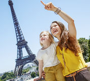 Mother and child pointing on something against Eiffel tower Stock Images