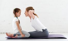 Mother with child practicing yoga in lotus pose Stock Images