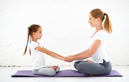Mother with child practicing yoga in lotus pose Royalty Free Stock Photos