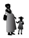 Mother and child. Pregnant woman standing with a child and talking on the phone Stock Photography