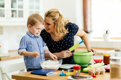 Mother and child preparing cookies Stock Photos
