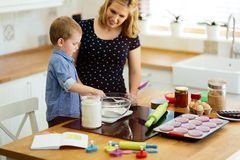 Mother and child preparing cookies in kitchen. Beautiful child and mother baking in kitchen with love stock photos