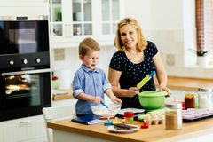 Mother and child preparing cookies in kitchen. Beautiful child and mother baking in kitchen with love stock photography